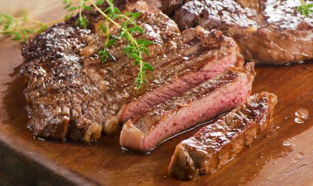 Beef steaks on a  wooden board.