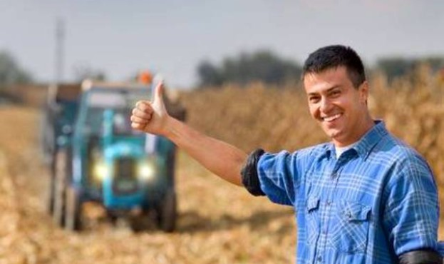 49205422-junger-lächelnder-landwirt-mit-daumen-nach-oben-als-ok-zeichen-auf-ackerland-traktor-mit-anhänger-im-hin
