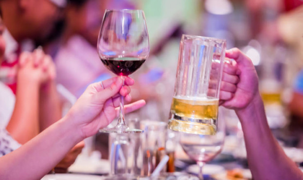 Group of unrecognizable people toasting with wine and beer. Friend toasting saying cheers