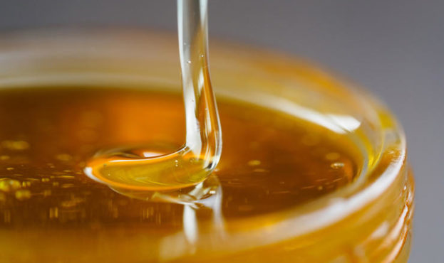 Honey falling in jar extreme close up