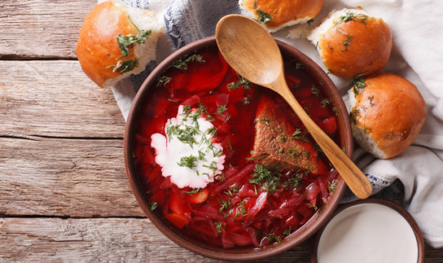 Ukrainian borsch soup and garlic buns on the table. Horizontal