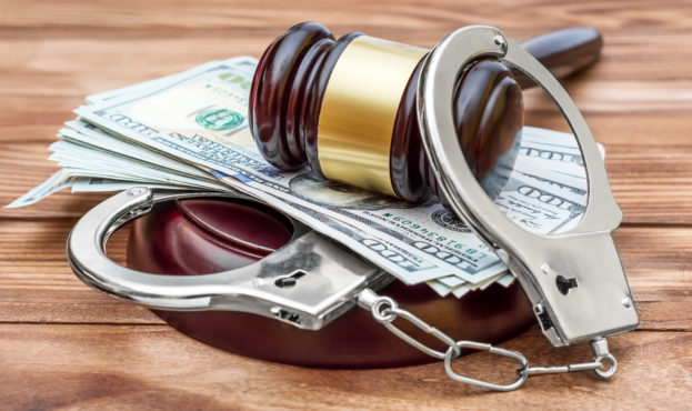 Gavel with handcuffs and money on the wooden table. Crime and law concept.