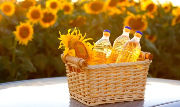 Three Bottles Of Sunflower Oil In A Wicker Basket Against Backlight