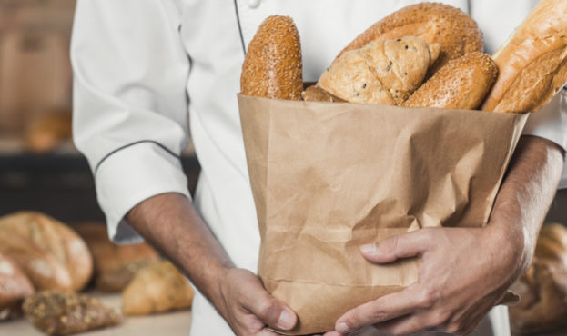 close-up-of-male-baker-s-hand-holding-baked-bread-in-an-paper-bag_23-2147883359