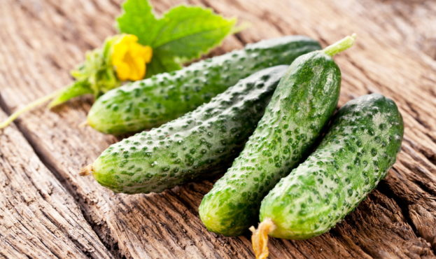 Cucumbers with leaves on a old wooden table.