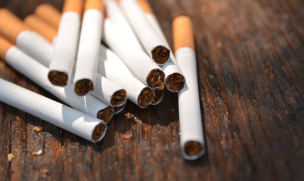 Tobacco cigarettes on wooden background with light shines on the