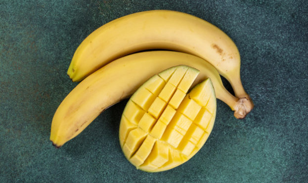 top-view-bananas-with-mango-on-green_141793-9541